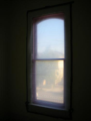 Accordion Room window draped in plastic